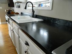 DIY:  Countertop Makeover - this blogger takes the fussiness & intimidation out of this project!  She painted her not-so-attractive white laminate using a kit & this is the result!  Tutorial.