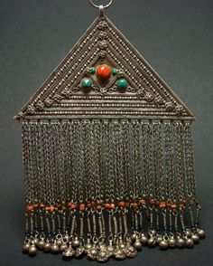 Afghanistan | Old triangular pendant; silver, with detailed embossing, turquoise and red glass paste cabochons.  Long fringe pendants decorated with coral beads | 340€