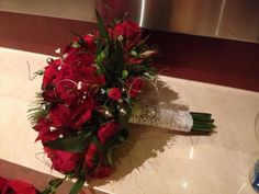 Holiday inspired bridal bouquet with red Alstroemerias, red rose sprays, red miniature carnations embellished with silver berries, tiny pine ones and silver Ting-ting.