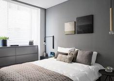 В главной спальне прикроватные светильники разные. Один - черный настенный, а второй, похожий на латунный кулон, свисает с потолка. .