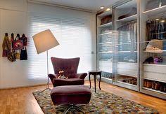 A área de vestir tem armários com portas de vidro deslizantes. Sobre o tapete da espanhola Nanimarquina, a poltrona e a mesinha dão o suporte ideal.