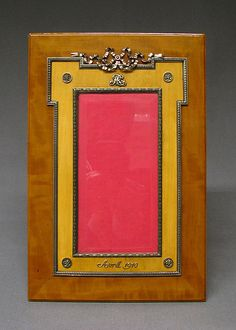 Picture frame by Carl Fabergé, workmaster: Karl Gustav Hjalmar Armfelt, 1908–17, in amaranth, fruitwood, and with silver ribbon mounts, silver monogram, and silver raised inscription 'Avril 1910'.