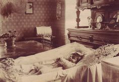 An unused real photo postcard showing an infant lying in a white-draped coffin in a parlour with heavy furniture.  Photographer and location unidentified, but bought from a German dealer, so probably European.~~~~Take note of her beautiful knitted dress.
