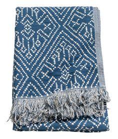 Mörkblå/Naturvit. En glesvävd pläd i bomullsblandning med tryckt mönster på ena sidan. Enfärgad baksida. Fransar längs med kortsidorna.
