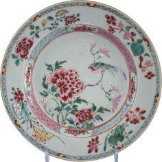 Assiette à décor d'un oiseau en porcelaine de Chine de la Compagnie des Indes d'époque Yongzheng Peintes dans les émaux de la famille rose, à décor d'un oiseau sur une branche parmi des fleurs de pivoines. Sur le marli, frise de treillages. Sur l'aile, des jetés de fleurs.
