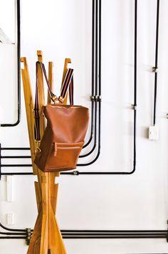Detalle de instalación eléctrica expuesta en el loft industrial de un diseñador de moda francés en Villa Crespo. Perchero de madera sobre pared en puro blanco.