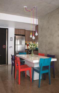 Sala de jantar / cimento queimado / mesa branca / cadeiras coloridas / luminárias coloridas / cozinha integrada