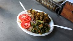 curried goat with steamed callalou, a traditional Jamaican delicacy.