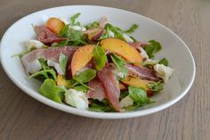 Salade van perzik, rucola, mozzarella, pijnboompitjes en prosciutto crudo
