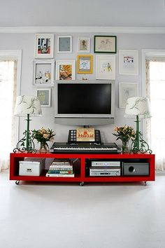 TV Wall- mostly white frames and white mats; color is used sparingly in the art and in the frames