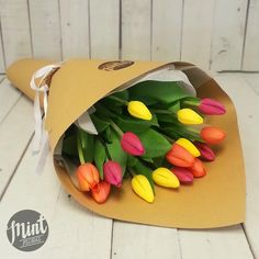 15 Mixed bright tulips spiraled with foliage and wrapped in tissue and natural…