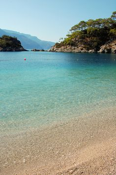 """""""Ölüdeniz remains one of the most photographed beaches on the Mediterranean. It has a secluded sandy bay at the mouth of Ölüdeniz, on a blue lagoon. The beach itself is a pebble beach. The lagoon is a national nature reserve and building is strictly prohibited."""" -Ölüdeniz Beach, Turkey"""