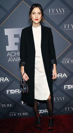 Alexa Chung wears a long blazer, midi dress, sheer tights, and red heels