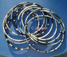 Catherine Jacquet -  Série des transformateurs   Série de cercles tour de cou. Différents diamètres, et couleurs. Fabrication à base de petits morceaux de cables électriques soudés