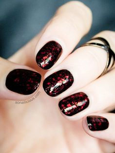 A Bloody Good Idea  Give your black polish an eerie upgrade with dark red glitter — it's a subtle nod to Halloween without being too over the top.