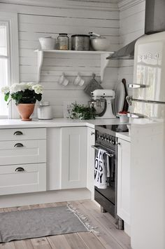 Love the clean space-saving cottage kitchen design. The shelf with with bracing bar across for holding cups or stabilization.