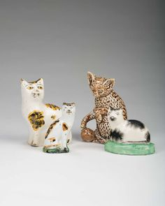 THREE STAFFORDSHIRE POTTERY AND PORCELAIN MODELS OF CATS, NINETEENTH CENTURY.