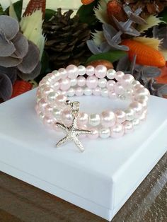Pearl memory wire bracelet. Pretty glass pearls in light rose / pink and white and a silver plated starfish charm adorning the end. Silver plated memory wire. Pearls have a smooth polished finish. Beautiful gift for the beach friend or you. Measurements: beads - 6 mm to 8 mm charm - 5/8 in length - 2 wraps Enter my shop here: https://www.etsy.com/shop/beachseacrafts Read what my customers are saying: https://www.etsy.com/your/shops/bea...