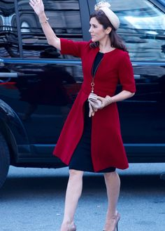 Crown Princess Mary of Denmark in a navy dress, red coat and tan straw calot hat at the opening of Parliament October 4, 2011