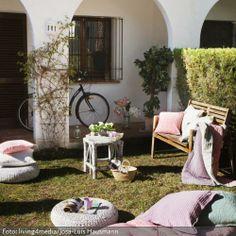 Um einen Vorgarten zu gestalten, muss dieser nicht groß sein. Mit verschiedenen Sitzgelegenheiten kann man ihn in voller Größe ausnutzen. Die Sitzkissen auf der Sitzbank, die rosafarbene Matratze und die Sitzpoufs in dem Vorgarten sind farblich aufeinander abgestimmt. Zudem können sie flexibel ausgetauscht oder wieder weg geräumt werden, sobald die Sonnen aus dem Vorgarten verschwunden ist.