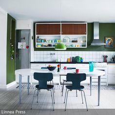 Die dunkelgrüne Wandfarbe grenzt im offenen Wohnraum den Küchenbereich farblich ab. Das Grün wird zur wunderschönen Bühne für den Küchenhängeschrank im…