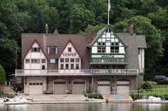 Boathouse Row - Philadelphia. Malta Boathouse on the right founded in 1860. Restored 1900 prize winning Octuple scull boat hangs upside down in wood-paneled men's locker room on 3rd floor. Historic rowing ribbons, trophies, and medals festoon interior as club members get on with preparing to win more.