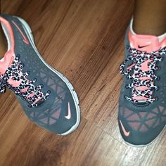 Gray and pink Nike running shoes with cheetah print laces