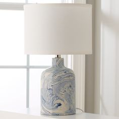 Indigo ceramic table lamp. Base is painted in cobalt and indigo to sky blue and white. Linen white shade. Handmade. No two alike. Coastal style, casual style, transitional style.