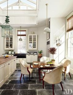 The kitchen's glazed cabinets were fashioned from antique windows; above the island hangs a copper lantern, and the drop-leaf breakfast table is Federal.