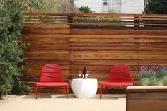 Horizontal fencing in the garden looks luxe and fresh #redchairs #fencing #gardendesign