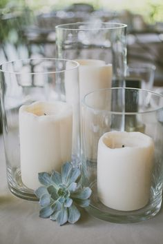 A trio of LED pillar candles in vases with pale green succulents tucked in between; surrounded by varied heights of silver mercury glass LED votives STEMS Floral Design www.stemfloral.com
