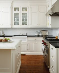 A traditional New England-style kitchen is always in fashion. Glass doors lighten up the expanse of Shaker cabinetry. For the countertops, the designer chose honed Nero Assoluto black granite, and hon