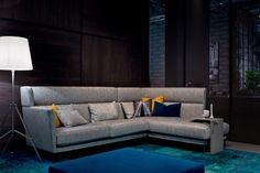 A MODERNE highback sofa in a sleek and sophisticated grey. Clean design lines and a quirky shape.