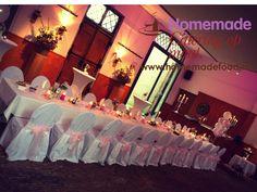 Huwelijksdiner opstelling aan 1 lange tafel in de Grote Salon van het Koetshuis van Kasteel Keukenhof. Wit linnen, wit afgerokte stoelen met roze strikken en witte en roze bloem decoratie, rozenblaadjes en stomp kaarsen op tafel. Homemade Catering op Maat denkt graag met u mee.