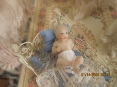 Susan's OOAK porcelain baby. This baby boy is my favorite! Monica Devine made his crib. He came with a mother from Susan also. Louise Glass