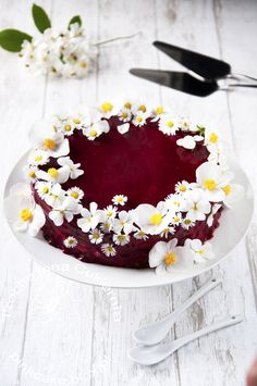 Pansies, daisies and begonias cake with rose cream and raspberry glaze