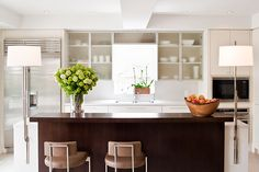 Powell and Bonnell Design Inc.  Ultra modern but also classical kitchen. Open concept and beautiful lighting and counter materials.