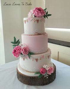 Pretty pink wedding cake with hand painted bunting, edible lace and beautiful sugar flowers including fluffy peonies, roses and babies breath. Wedding cake created by Lucie Loves To Bake #lucielovestobake wedding cake maker creating beautiful bespoke wedding cakes across the New Forest, Hampshire and Dorset