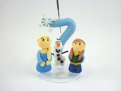 Vela decorada personalizada Frozen, contendo 01 Número e 3 miniaturas (Elsa, Anna e Olaf).    Produto sob encomenda. Consulte prazos de produção e envio.  Valor unitário.    Material: biscuit; base acrílica transparente; pavio de vela mágica estrelada.  Altura aproximada: 9cm + pavio. R$ 35,00