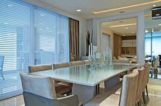 na sala de jantar, optei pelo modelo de mesa LIFE ( LACA BRANCA BRILHANTE E CRISTAL LAQUEADO BRANCO), também da Breton. As cadeiras são modelos LIZA sem braço em laca cinza brilhante e tecido velvet bamboo. Essa combinação deixa a sala com um aspecto muito elegante e acolhedor.