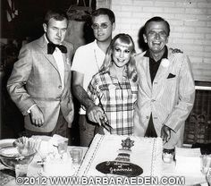 """""""I Dream of Jeannie"""" cast members (left to right) Bill Daily, Larry Hagman, Barbara Eden and Hayden Rorke celebrate the 100th Episode of I DREAM OF JEANNIE. This shot was taken on the set; you may notice the fireplace of the Nelson living room behind them. You may also notice the sound stage behind them on the left hand side of the photo."""