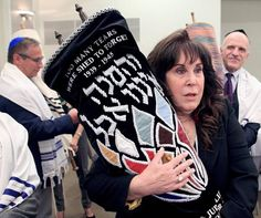 Lynn Strauss walks with one of the 26 rescued Holocaust Torahs at the start of the presentation at Hollywood's Temple Beth El.