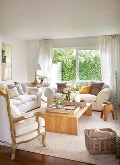 00410768. Salón decorado en blanco con detalles en marrón y naranja con un ventanal con vistas al jardín_00410768