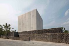 Peaceful and solemn, the pure white volume of this chapel in Suzhou, China, invites the visitor to approach, enter and pray. Designed by Shanghai-based studio Neri&Hu, the chapel is a prominent new addition to the village's skyline, visible both from the main street and the adjacent lake.