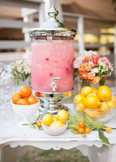 Create a vignette with a beverage dispenser and glasses. It'll look super cute and guests can serve themselves a refreshing drink. What's better then pink lemonade in the summertime? #summerwedding #beverage