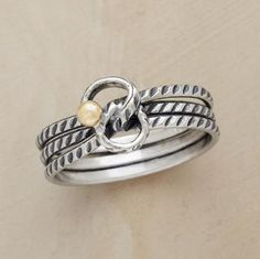 Dotted with a 14kt bead, the symbol for infinity poses never ending possibilities. It joins three wavering bands in our exclusive design. Sterling silver. Whole sizes 5 to 9.