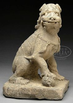 """CARVED STONE LION. Five Dynasties Period (907-960), China. Carved from sandstone or similar stone depicting a seated animal on base posed with brocade ball beneath right paw. SIZE: 28"""" h. PROVENANCE: From a private New York State collection."""