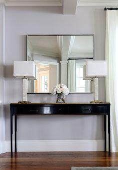 Chic foyer features a glossy black console table with black pulls accented with a gold top alongside mirrored lamps placed under a mirror.