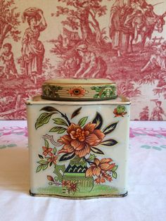 Vintage Tea Tin with a pretty pinky coral, green and black floral design on an robins egg blue and white background. Its in excellent condition