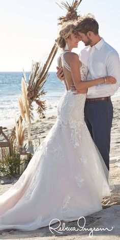 Affordable Wedding Dresses - Rebecca Ingram Elizabetta | Backless mermaid bridal gown with halter neckline, keyhole back and trumpet skirt | Romantic beach destination wedding photo of boho bride and groom  - Belle The Magazine #weddingdress #weddingdresses #bridalgown #bridal #bridalgowns #weddinggown #bridetobe #weddings #bride #dreamdress #bridalcollection #bridaldress #dress See more gorgeous bridal gowns by clicking on the photo Colored Wedding Dresses, Dream Wedding Dresses, Designer Wedding Dresses, Bridal Dresses, Wedding Gowns, Affordable Wedding Dresses, Dresses Dresses, Blush Gown, Sheath Wedding Gown